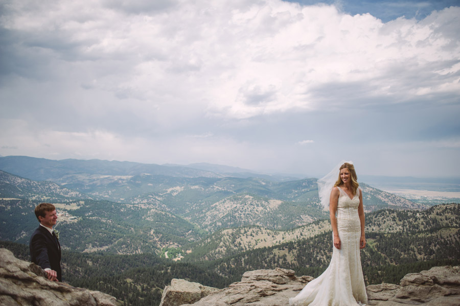 groom happily stares at his bride in front of the foothills of boulder