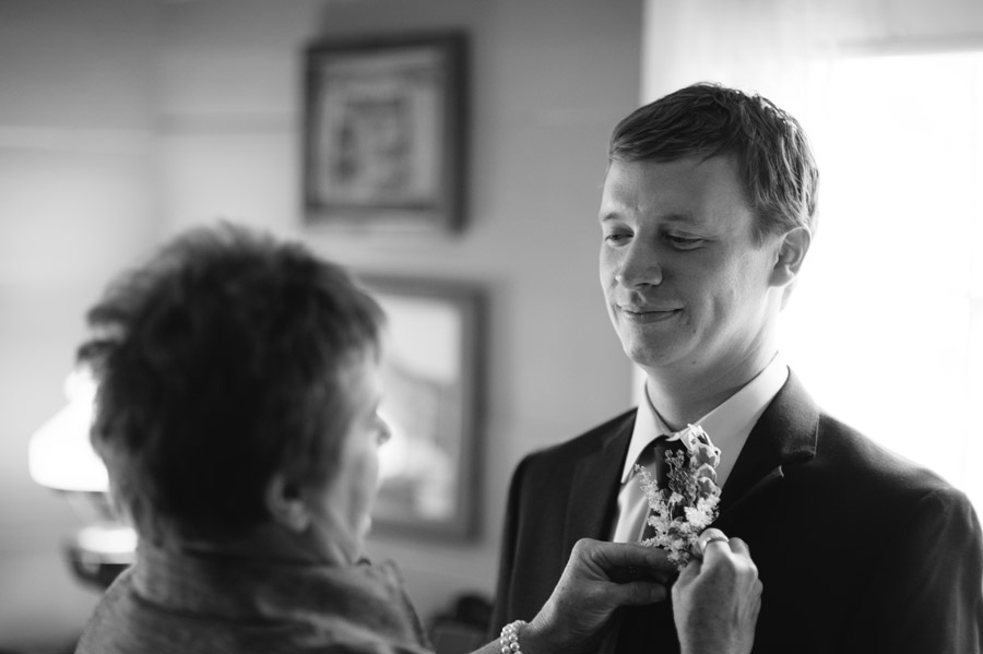 mother of the groom helping him get ready for wedding