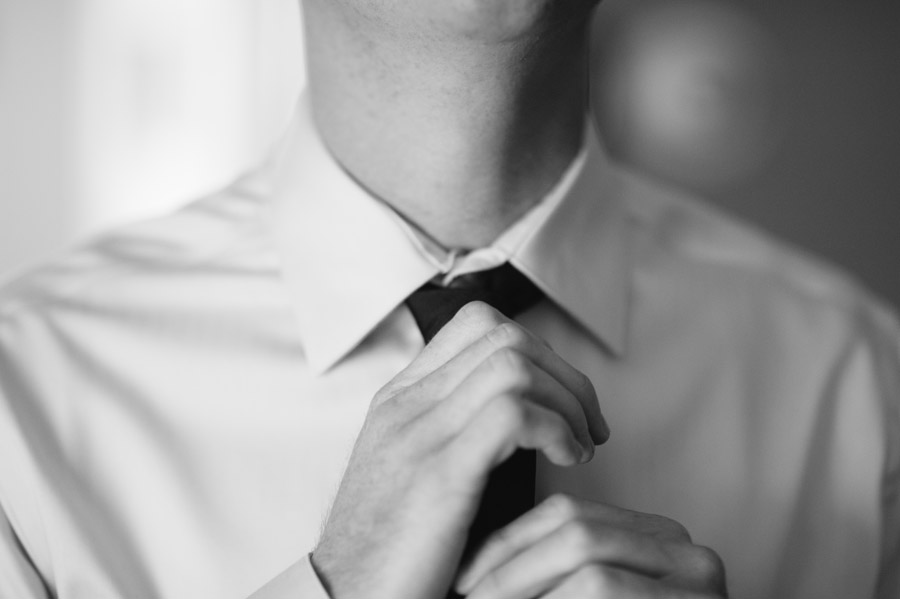 groom fixes his tie before wedding in boulder, colorado