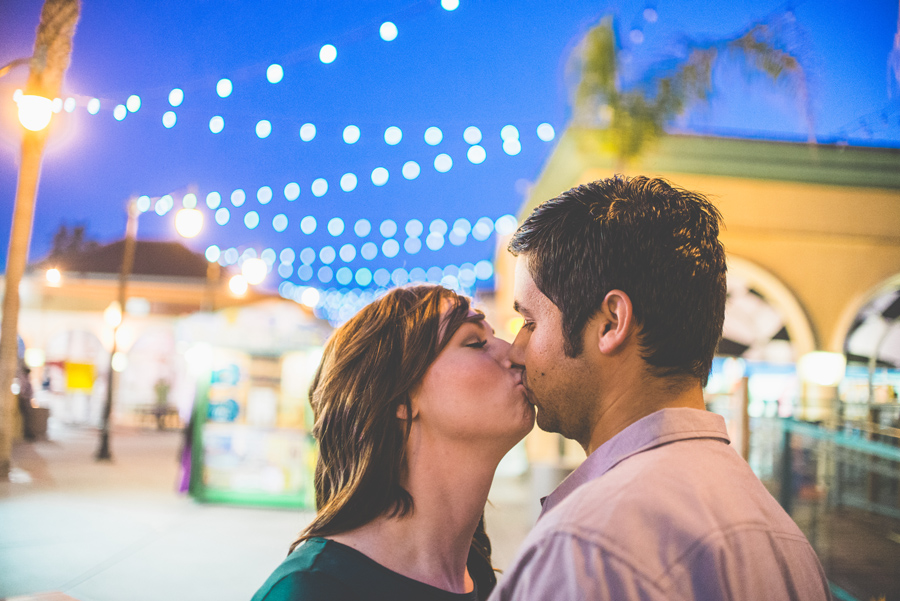 newly engaged couple kiss under the lights of belmont park, dan hand photography