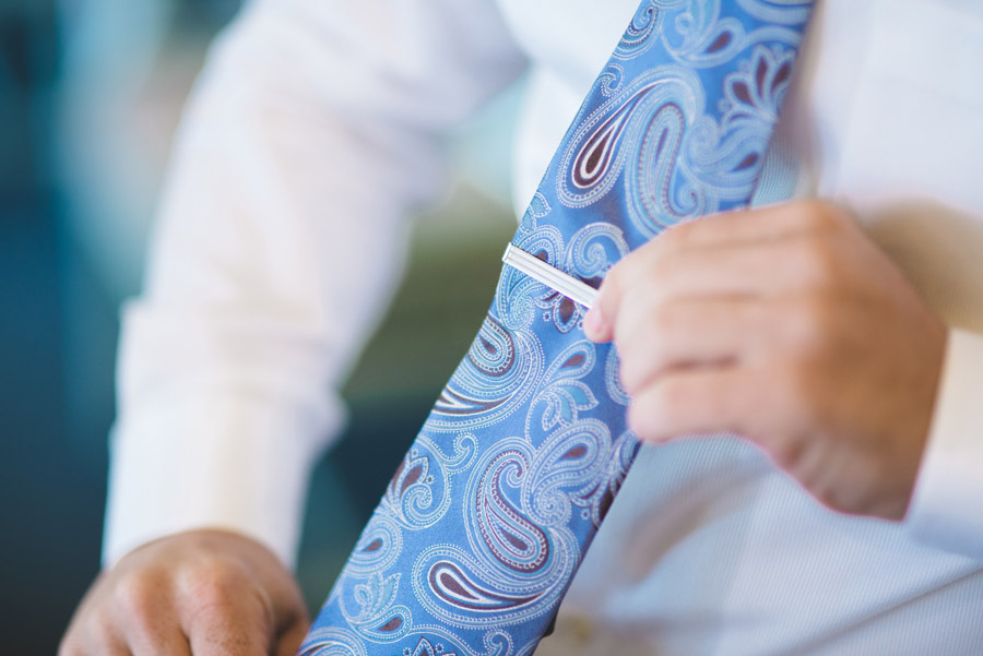 groom puts tie clip on paisley tie before wedding