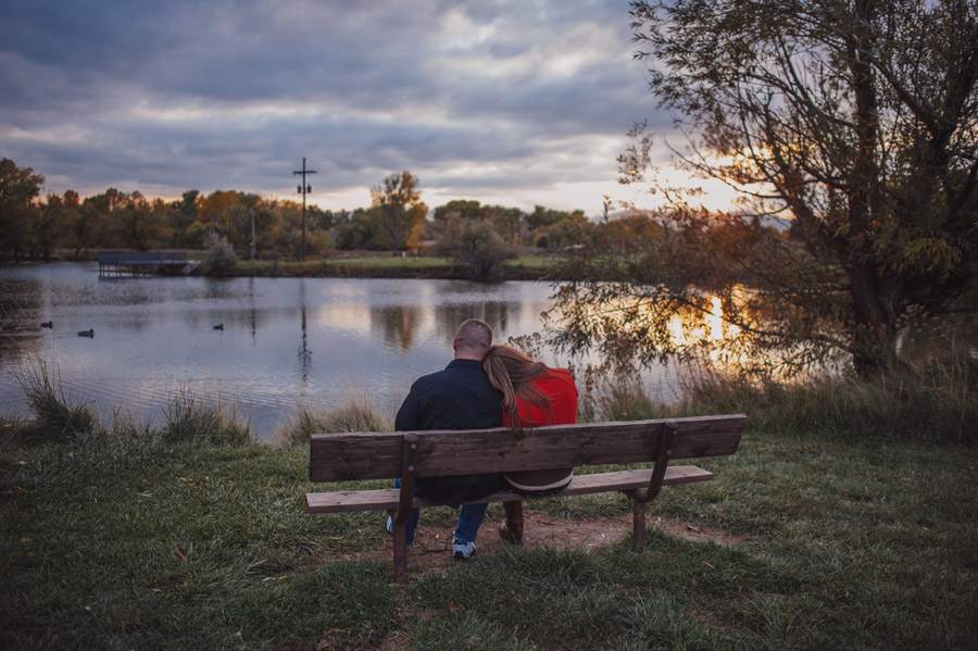 engaged couple sits on a bench watching fall sunset at bear creek greenbelt