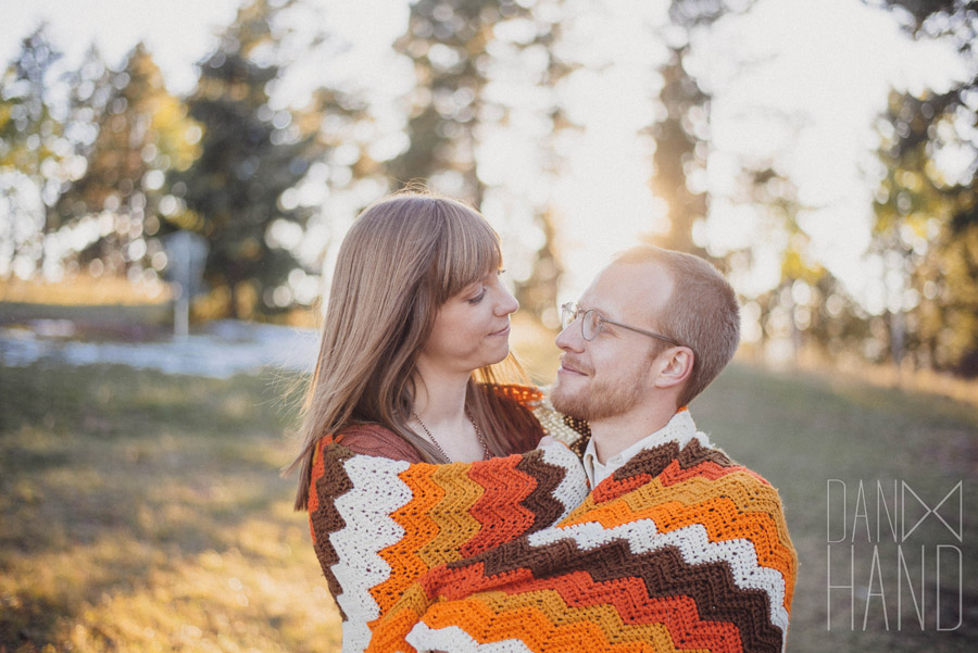 engaged couple share a blanket in the colorado mountains