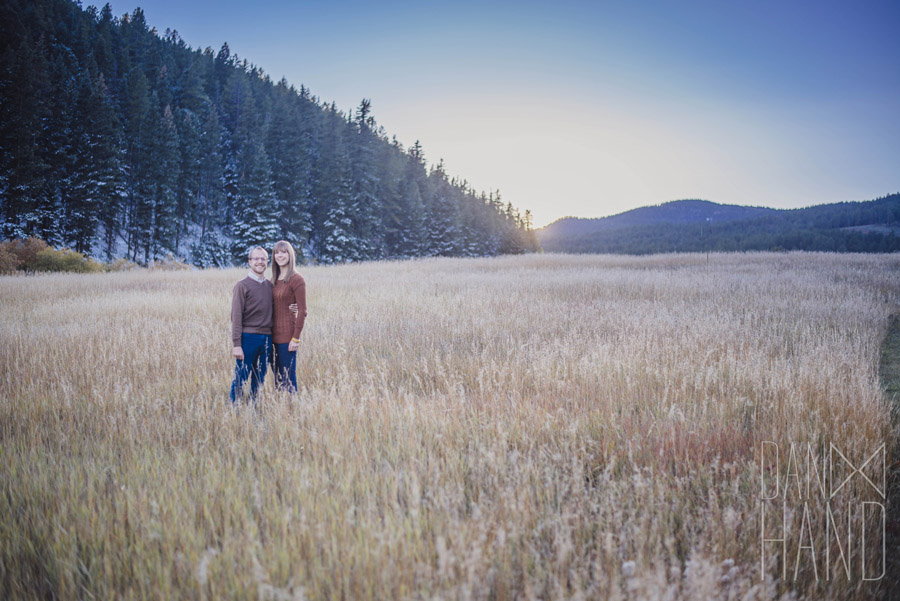 engagement photo in a field as the sunsets in the mountains near denver
