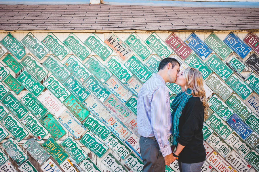 couple kiss in front of license plate wall in Morrison Colorado by Colorado Engagement Photographer