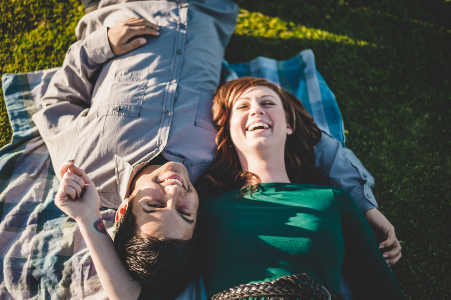 couple laughing while laying on grass during san diego engagement session
