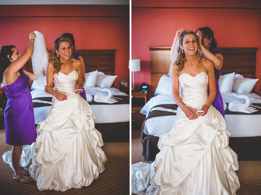 laughing bride is helped into dress by bridesmaid