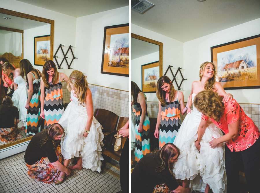 bridal party helps bride put her shoes on at the d-barn