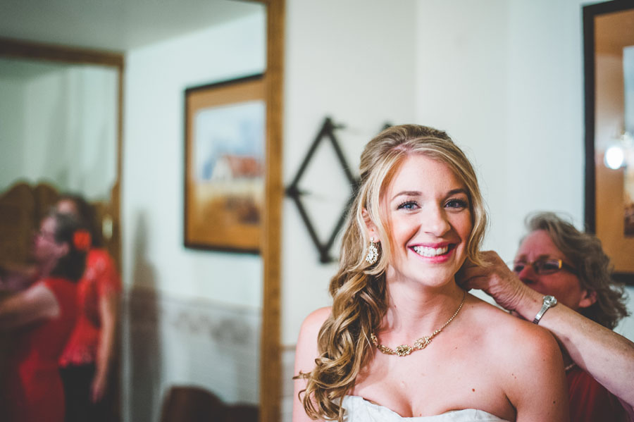 bride's mother helps her put her necklace on