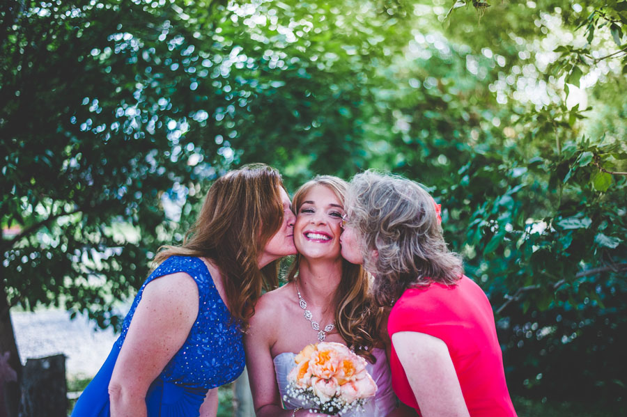 smiling bride kissed by mother and mother in law