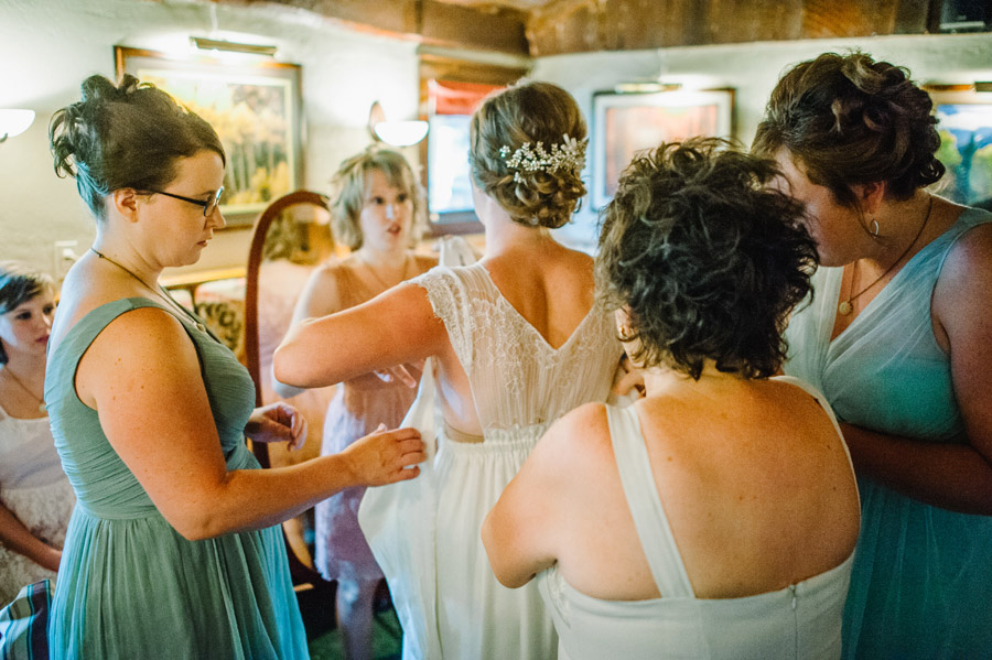 bridal party helps wrap bride in vintage dress in boulder colorado