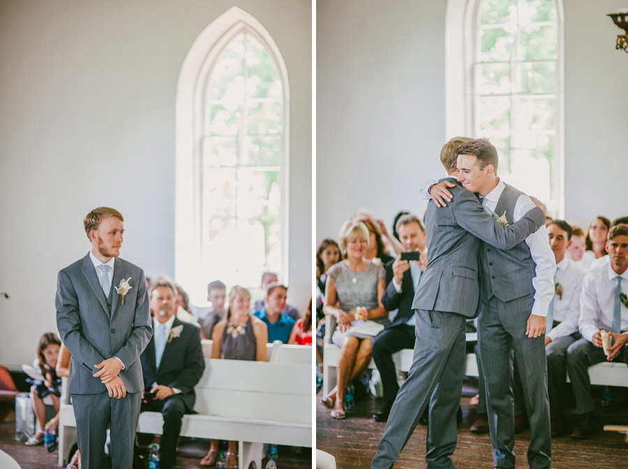 Groom and best man embrace during wedding processional