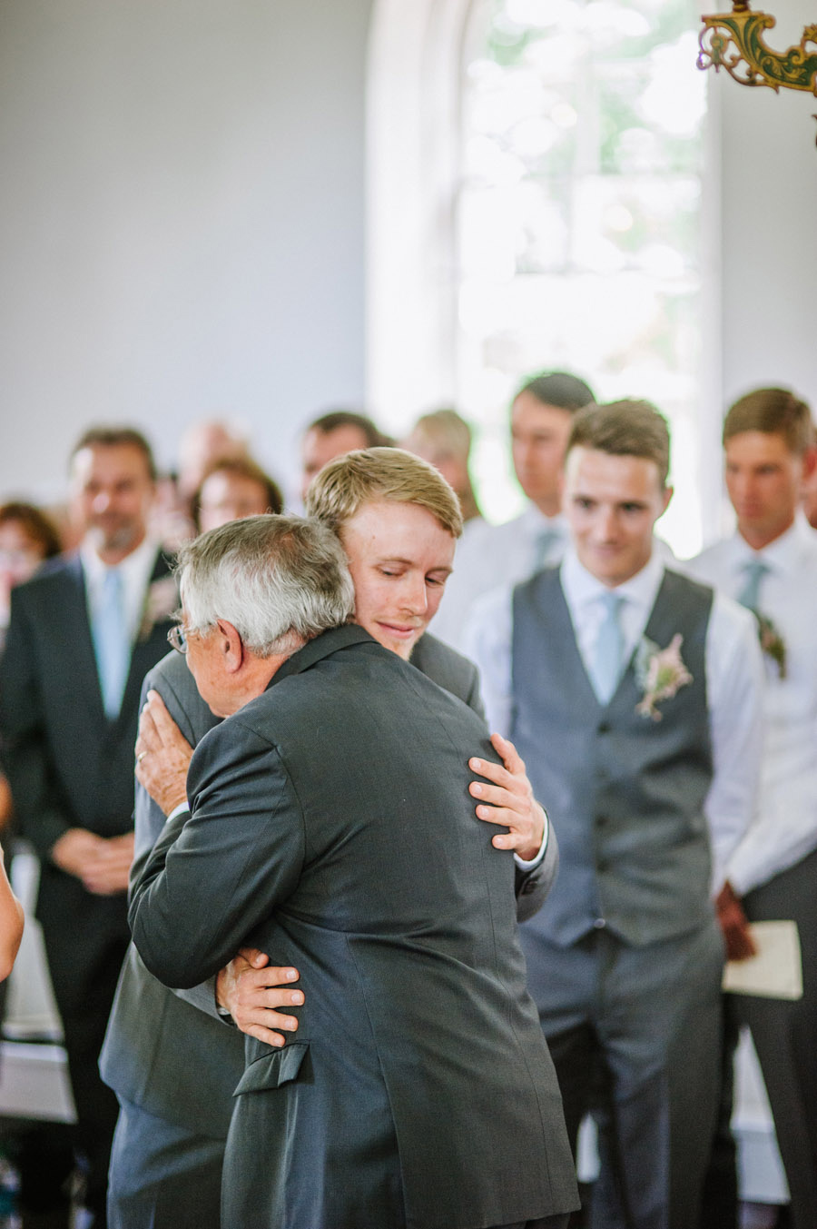 father of bride and groom share a moment during wedding in ryssby church