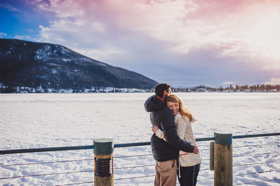 Engaged couple hugging in front of a frozen Grand Lake in Colorado