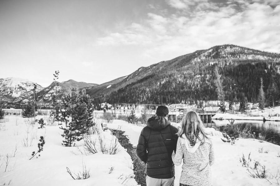 couple walks along a frozen path near grand lake