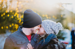 couple kissing with christmas lights in the background