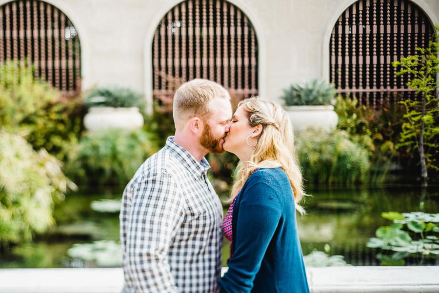 engaged couple kissing in Balboa Park