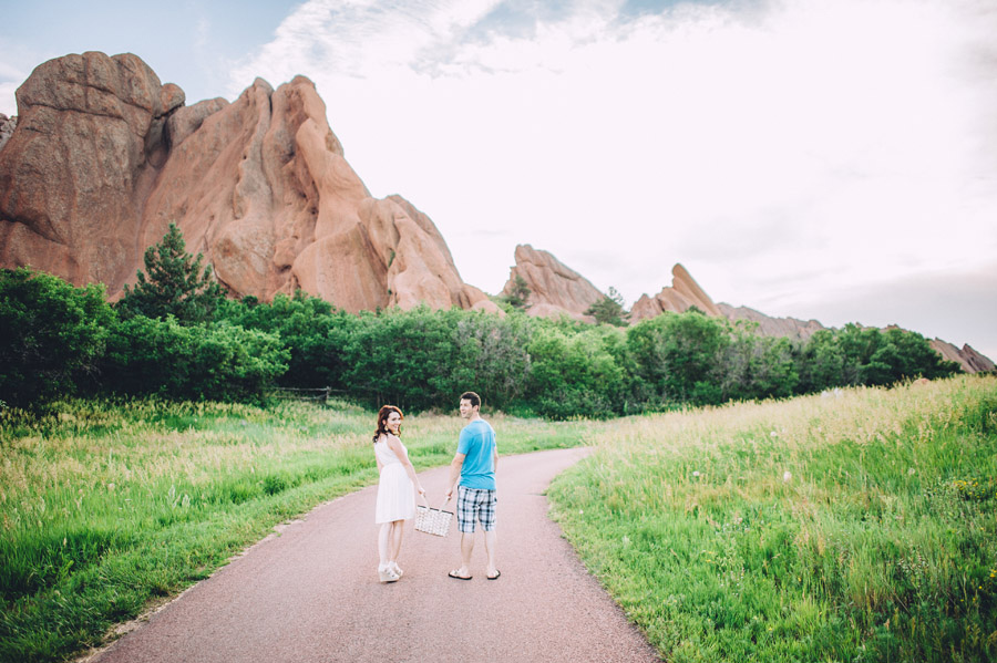 couple walking on path towards rock formation in roxborough park
