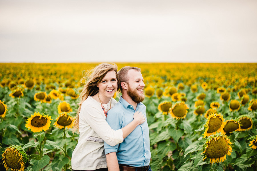 Beautiful couple poses among giant sunflowers in the Denver Sunflower Fields by the Denver International Airport