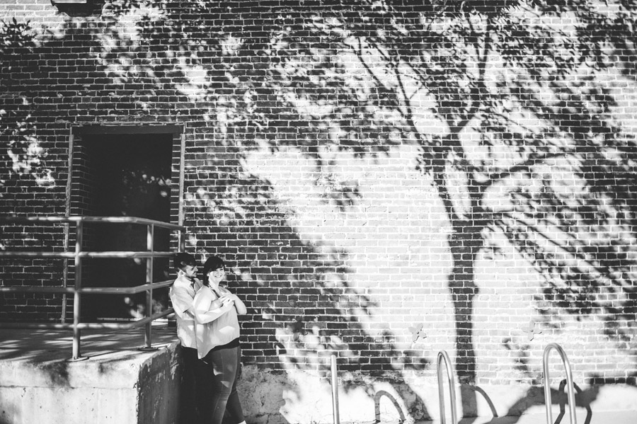 couple posing for photo next to silhouette of a tree on a brick wall