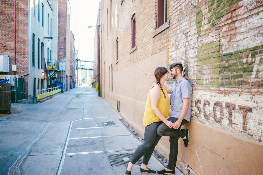 couple leaning against brick wall in a downtown denver alley
