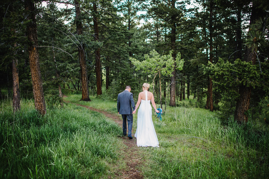 bride and groom walk through the trees of genesee colorado