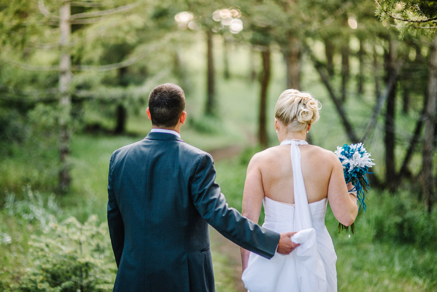 groom helps bride carry her dress through a forest path