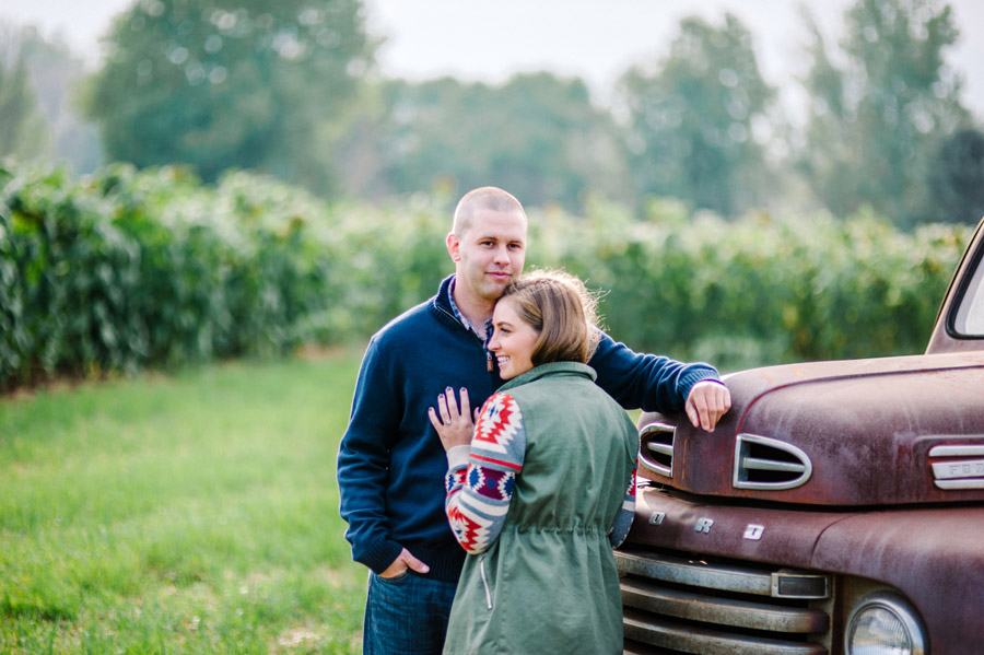 couple poses near old pickup truck at isabelle farms in boulder colorado