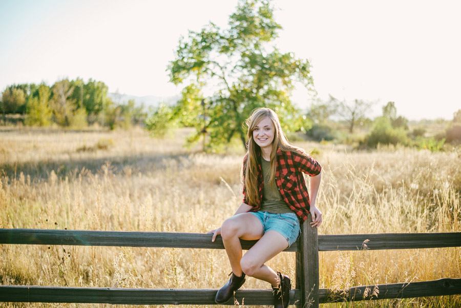 girl sits on a wooden fence for senior photos in denver