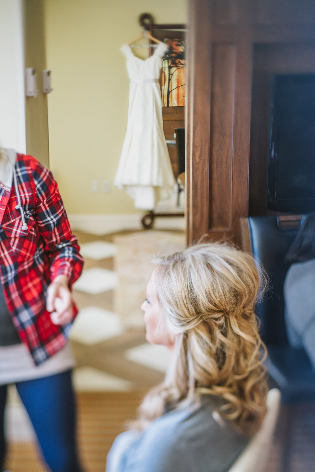 bride having makeup done with wedding dress hanging in background