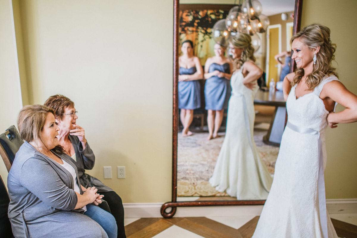mom and mother in law overwhelmed at seeing bride in dress