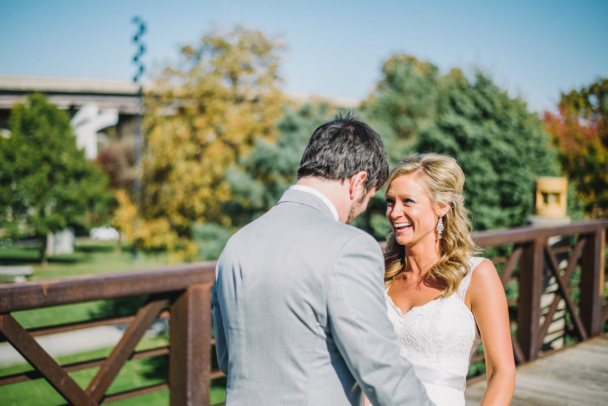 excited bride and groom laugh during first look