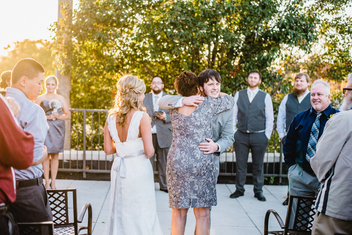 groom hugs mother of bride during wedding ceremony