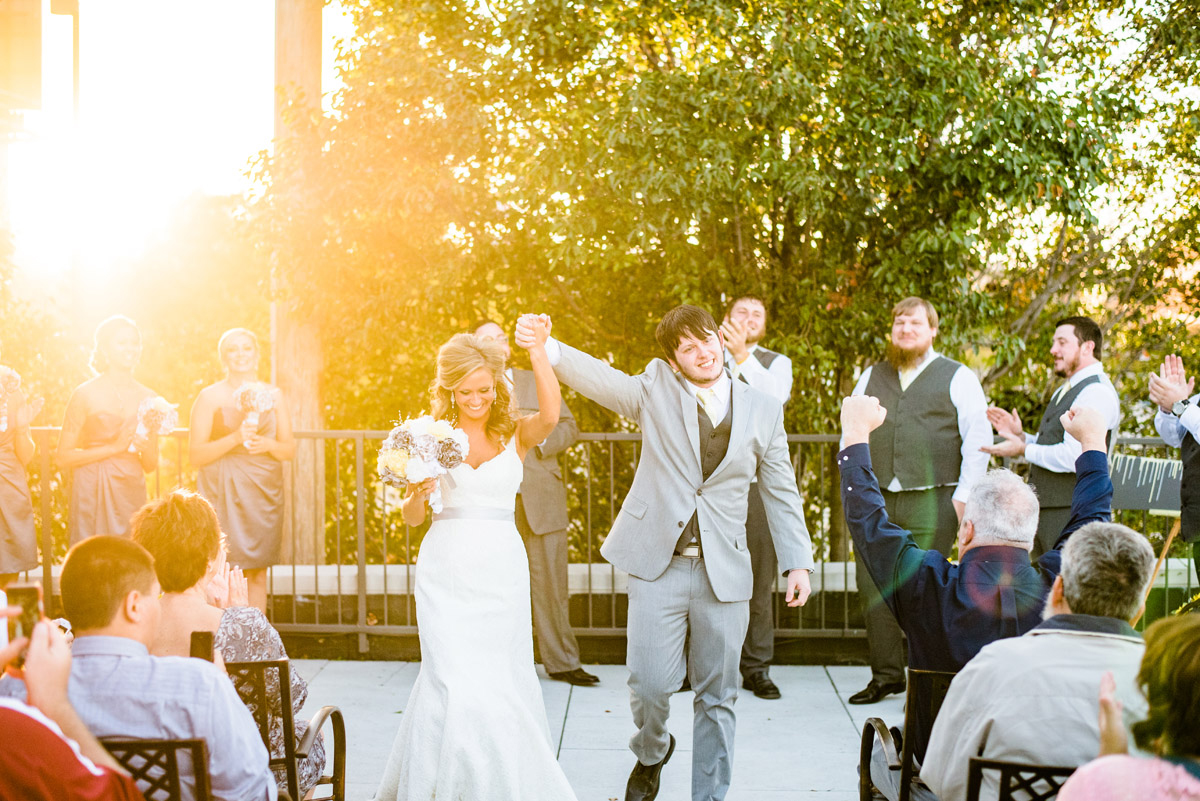 bride and groom leaving wedding ceremony in omaha at the old mattress factory