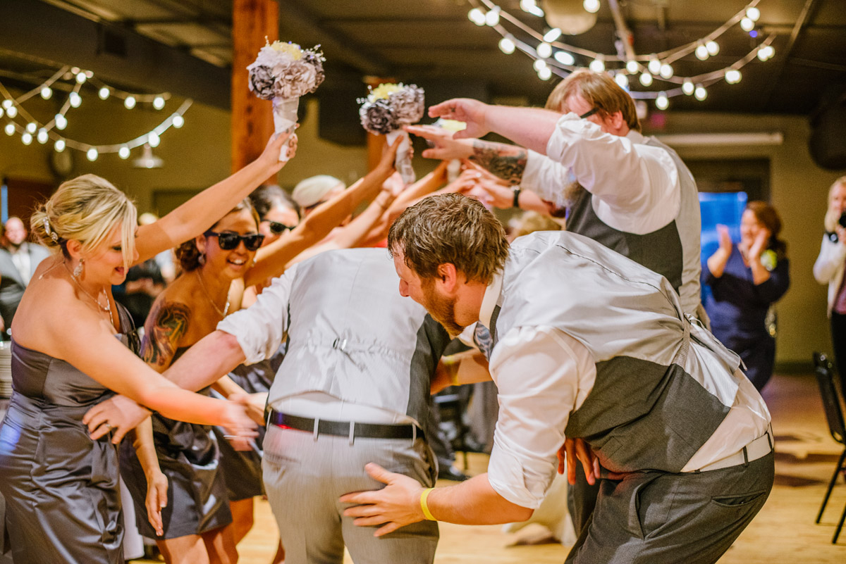bridal party greets the bride and groom with a gauntlet