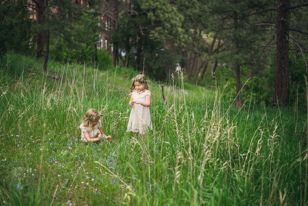 flower girls picking wildflowers before estes park wedding