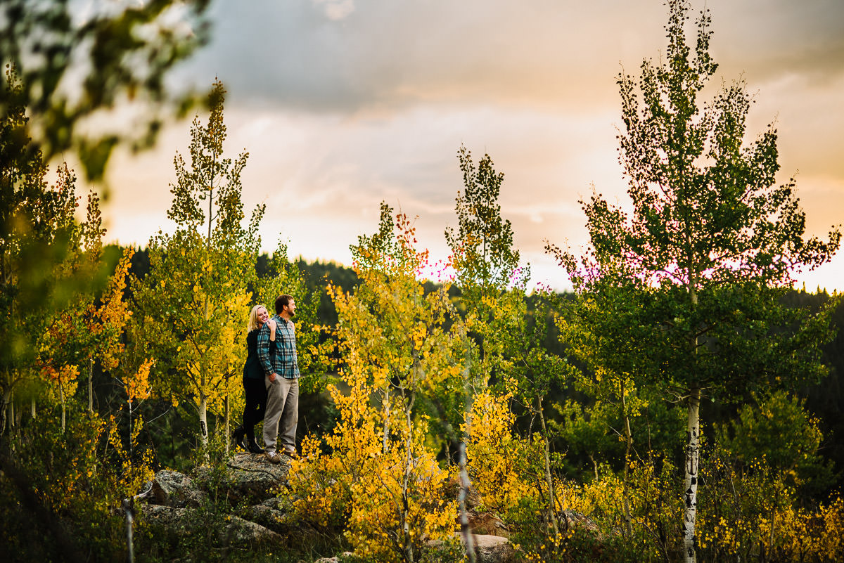 engagement photo of couple on a rock overlooking kenosha pass