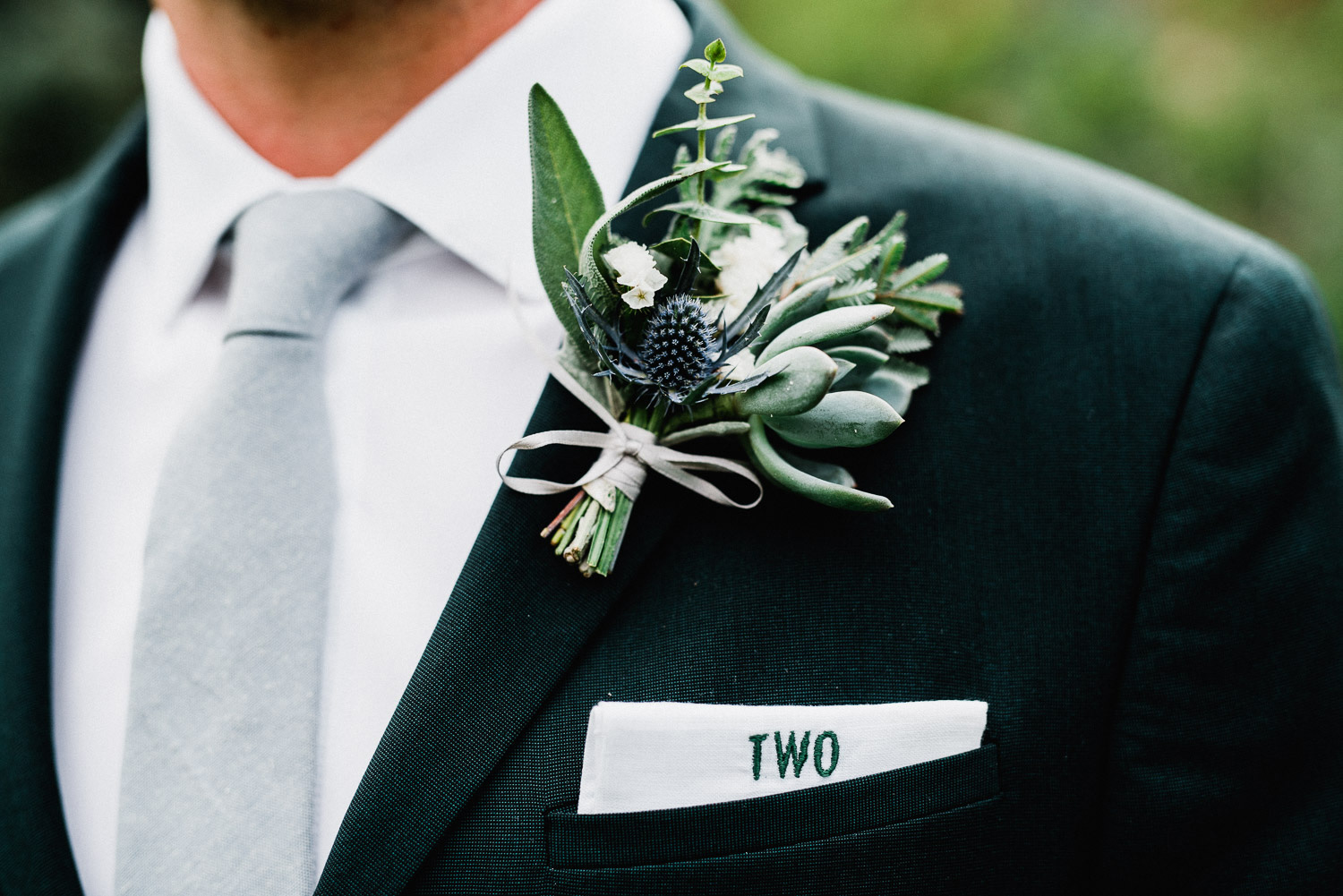 Groom with monogrammed pocket square and boutonniere at the river bend in lyons, colorado