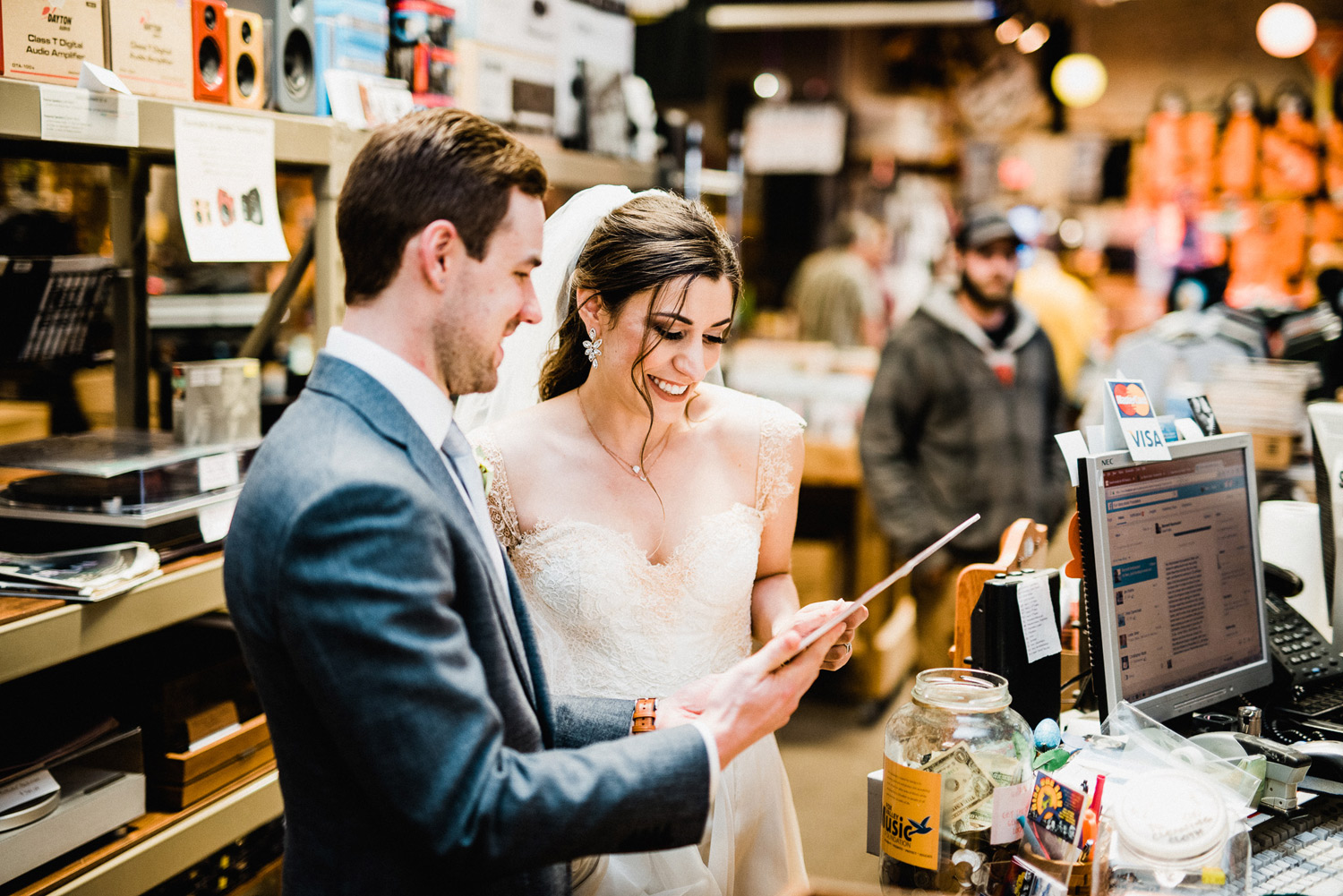 newlyweds buying album at kiss the sky records on their wedding day